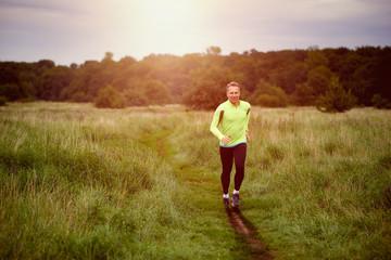 Fitter muskulöser Mann trainiert und läuft an einem Feldweg