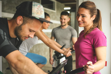 People exercising on stationary bikes in fitness class. People workout in gym. People with personal trainer.