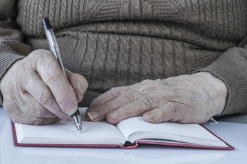 closeup wrinkled hands of a person writing