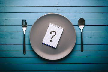 Empty plate with a question mark drawn on a notepad on a blue table, food concept