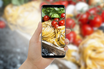 Woman hand taking photo of pasta and tomato with smartphone