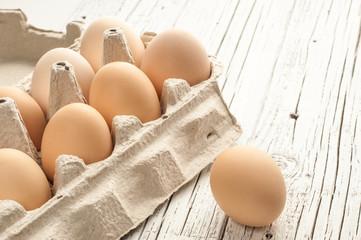 chicken eggs in cardboard box on white wooden background