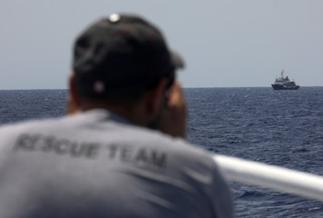Lifeguard from the Spanish NGO Proactive Open Arms looks at C Star vessel in the Mediterranean Sea