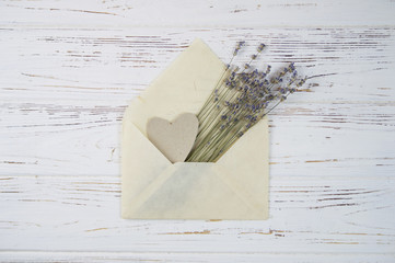 Bouquet of lavender flowers in a paper envelope on a wooden white background. romantic background