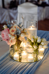 Fresh spring tulips and candles in glasses. Covered festive table. Bride idea.