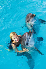 Coach swims in the water with dolphins. Dolphin Assisted Therapy