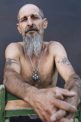 Portrait of a tattooed aged man