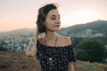 Tattooed young girl during a sunset