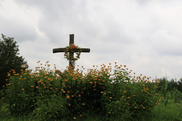 Orthodox cross among yellow flowers under the cloudy sky