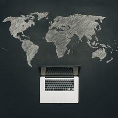 Laptop with a worldmap on a chalkboard