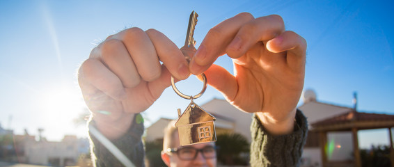 Property, ownership, new home and people concept. Cheerful young man holding house key.