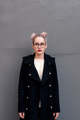 Girl in black coat on gray background.
