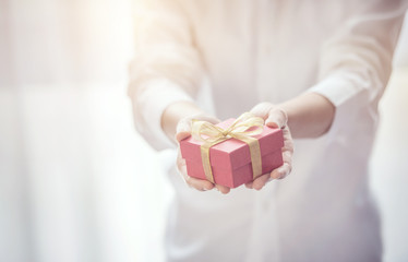 Closeup, Woman hand holding red gift box with copy space background, female giving gift, New year holidays and greeting season concept.