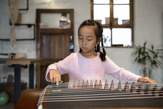 Adorable little girl playing zither at home
