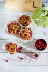 Red currant muffins on white plateau. White wooden table, gray background. Baking paper.