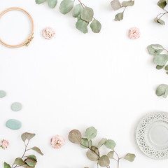 Flat lay border frame with eucalyptus branches, plate on white background. Top view floral background with space for text.