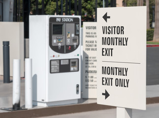 Automobile pay station visitor information sign. Focus on sign with words and arrows. Parking lot exit, blurred background.