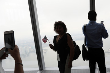 New citizen Mirna Murga, originally from Ecuador, waves a flag while taking a picture, after a U.S. Citizenship and Immigration Services (USCIS) Naturalization ceremony at One World Observatory in Manhattan, New York