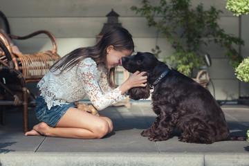 Girl playing with a brown English cocker spaniel dog