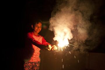 A teenage girl making fun with firecrackers
