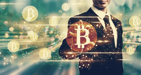 Bitcoins with businessman on blue tech background