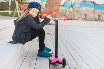 Blond little girl with a pink push scooter