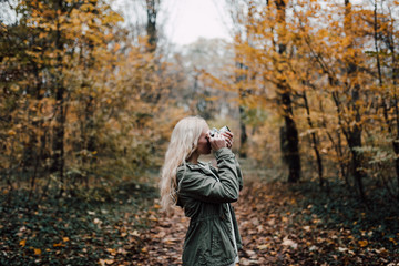 Blonde woman taking picture in nature during fall