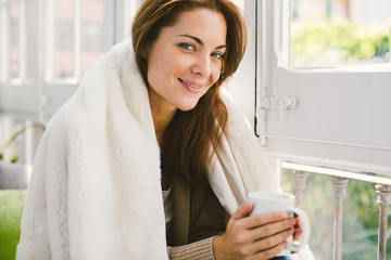 Mature woman drinking a coffee covering with blanket at home.