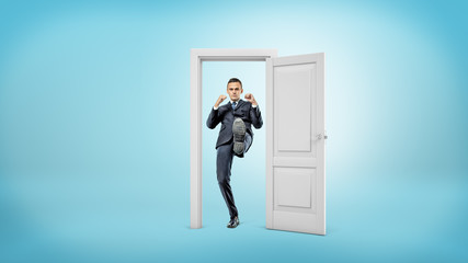 A young businessman stands in a small cut out doorframe and kicks a door open with his foot.