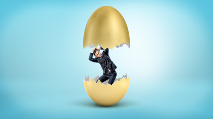 A small businessman revealed as just hatched from inside a cracked golden egg.