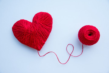 heart made of red wool yarn hanging on white background./heart shape made from knitting wool