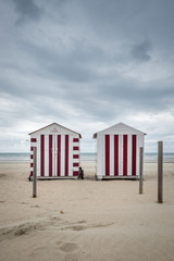 Two colorful beach cabins on a cloudy day in De Panne, Belgium.