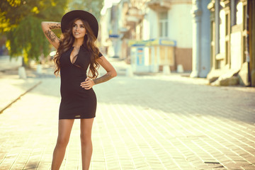 Portrait of a gorgeous glam tattooed lady with long wavy hair wearing a little black dress and trendy fedora hat standing on the street and smiling on a sunny day. Outdoor shot. Copy-space