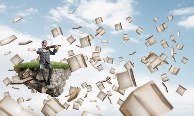 Handsome violinist play his melody and books flying around in sky