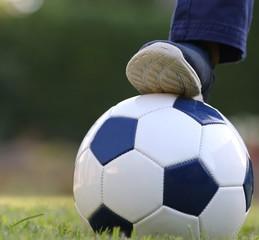 Engagement partie foot avec ballon bleu et blanc sur terrain de gazon