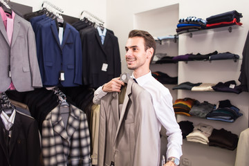 The man buyer chooses jacket the boutique