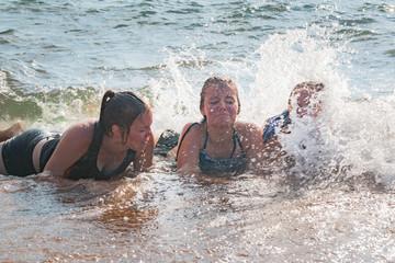 Waves Splash Girls Laying on the Sand
