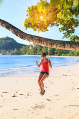 Beautiful young girl in In bright clothes sits on a swing under a palm tree on a tropical beach
