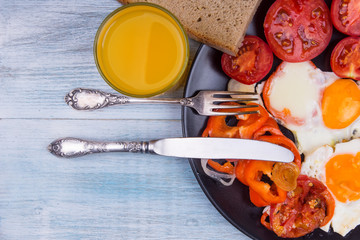 Fried eggs with tomatoes, onions and peppers and a glass of orange juice on a wooden shabby background