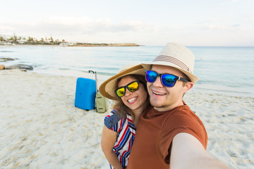 tourists couple taking selfie on the beach. Vacation, love, travel and holiday concept.