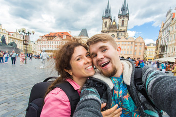 Happy romantic couple of tourists makes selfie self-portrait in Prague while traveling across Europe.