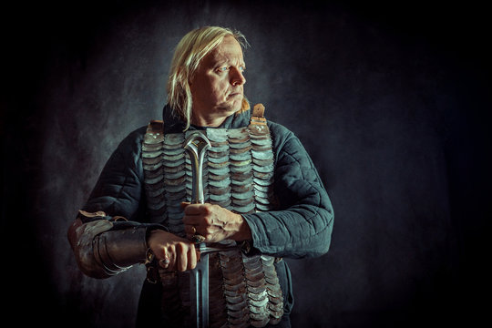 Powerful blond knight with the sword on the dark background.