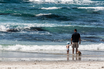 Man,boy and dog on beach