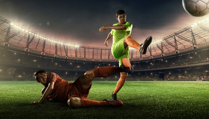 two soccer players on a soccer field fighting for a ball