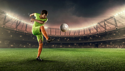 soccer player hits a ball on a soccer stadium with illumination lights and dramatic night sky