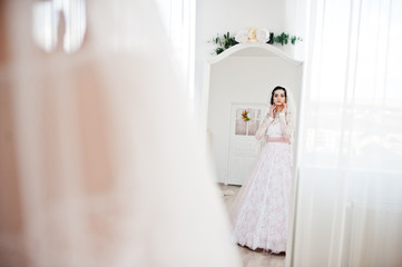 Pretty bride in outstanding wedding dress looking in the mirror in big white room.