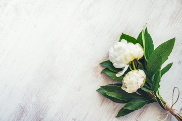 Top view of a bouquet of white peonies flowers over white wooden rustic background. Copy space.