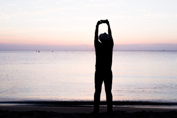 silhouette of a man holding a cellphone taking pictures outside during sunrise or sunset on the beach. Black light photo.