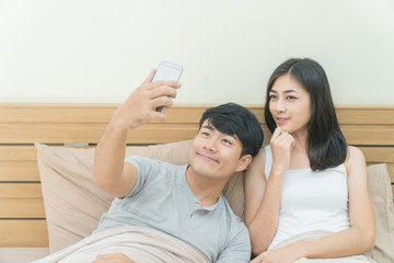 Young happy Asian couple taking selfie with smart phone on the bed