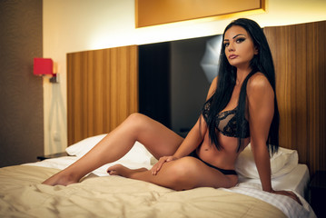 Attractive woman in sexy lingerie  in hotel room on bed.